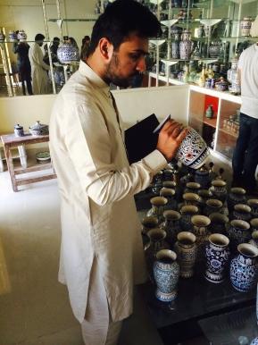 Farjad inspecting pottery work